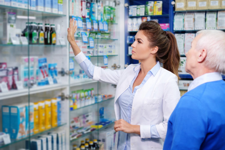 Beautiful young woman pharmacist showing drugs to senior man customer in pharmacy.